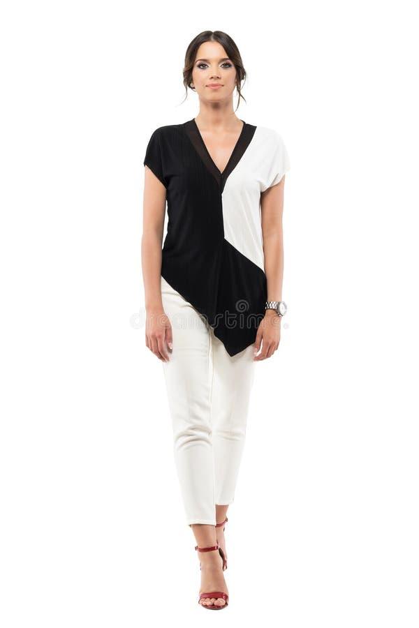 Szczęśliwa młoda elegancka biznesowa kobieta w czarny i biały kostiumu odprowadzeniu, patrzeć kamerę i zdjęcia royalty free