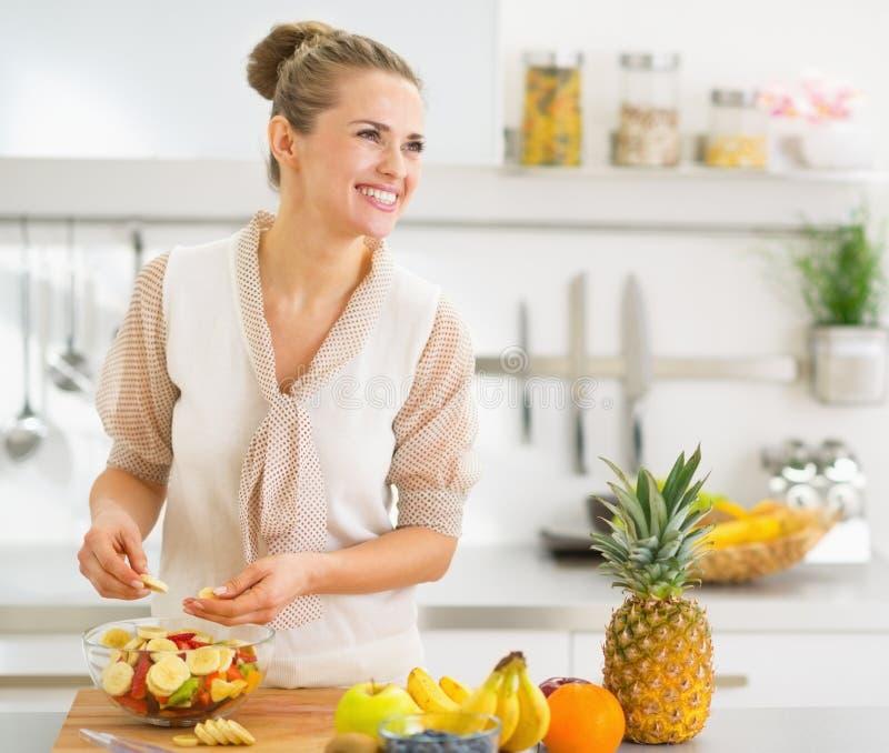 Szczęśliwa młoda gospodyni domowa robi owoc sałatki zdjęcia royalty free