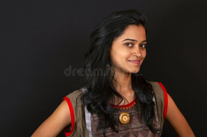 Szczęśliwa młoda Indiańska kobieta ono uśmiecha się przeciw czarnemu tłu, Pune, India zdjęcie stock