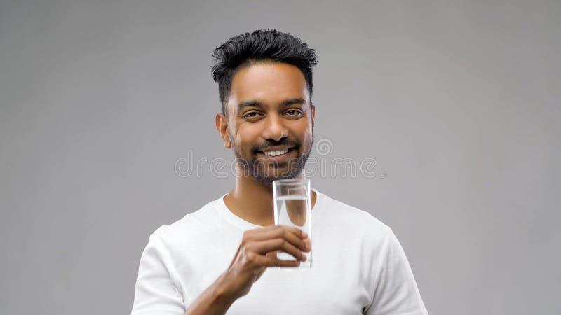 Szczęśliwa młoda indyjska mężczyzna woda pitna od szkła obraz royalty free
