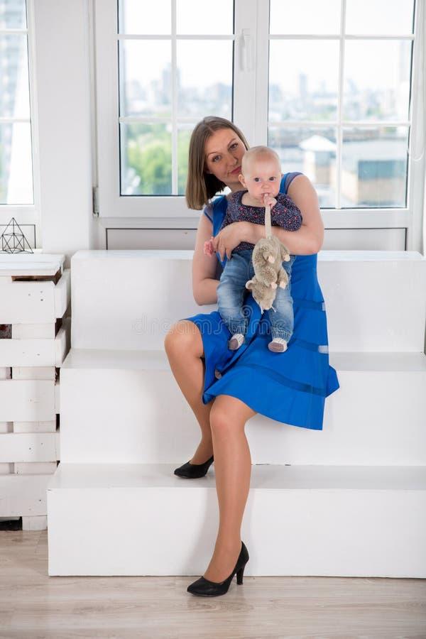 Szczęśliwa mÅ'oda kaukaska rodzina w Studio. Matka trzymajÄ…ca córkÄ™ w rÄ™kach. Dziecko niemowlÄ™ce trzyma konia. Siedzenie mÄ obraz royalty free