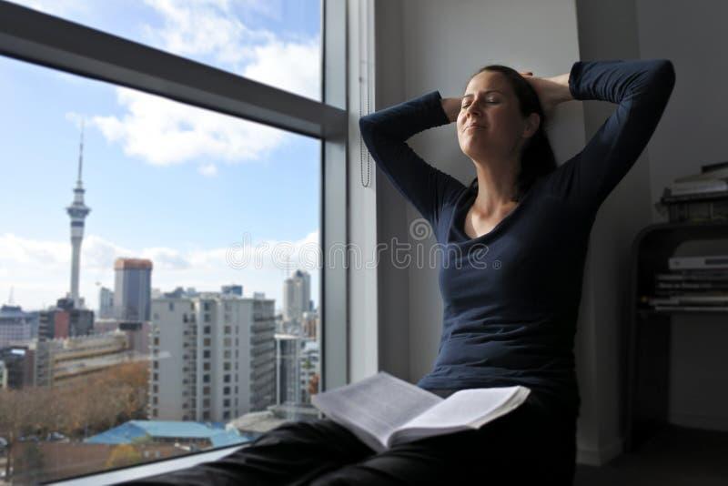 Szczęśliwa młoda kobieta czyta książkę zdjęcia royalty free