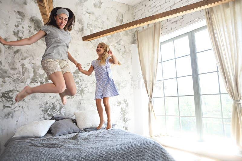 Szczęśliwa młoda kobieta i jej mała śliczna córka mamy zabawę wewnątrz obrazy royalty free