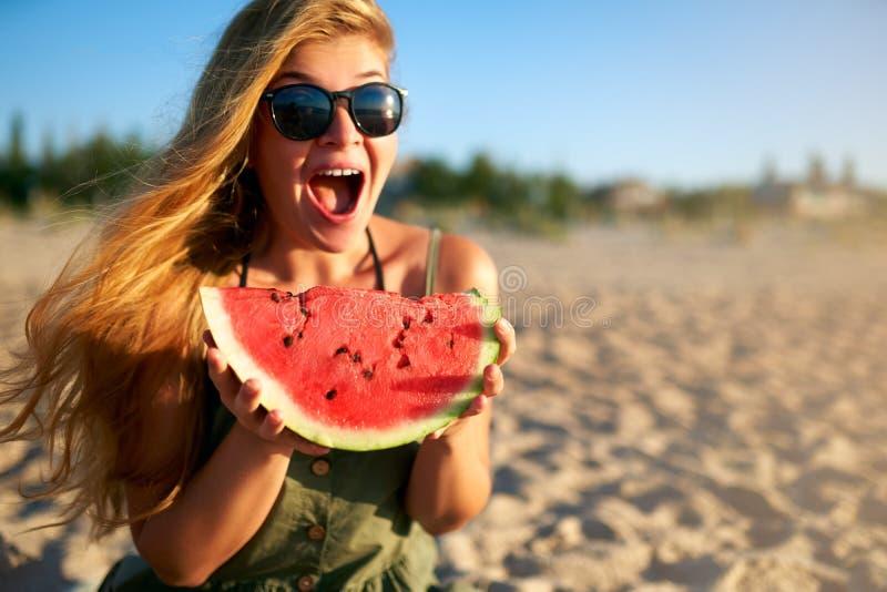 Szczęśliwa młoda kobieta je arbuza na piaskowatej plaży na wakacje w szkłach Dziewczyna joyfully trzyma świeżego arbuza fotografia royalty free