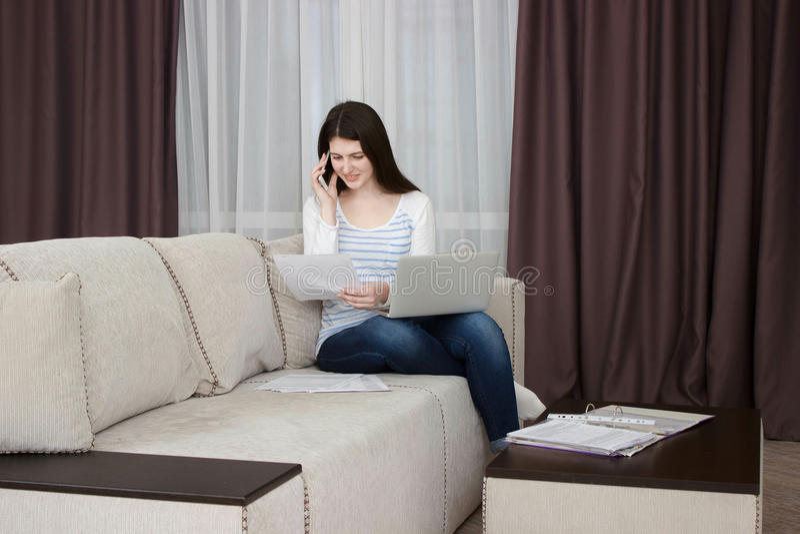 Szczęśliwa młoda kobieta jest relaksująca na wygodnej leżance i używać w domu laptop fotografia stock