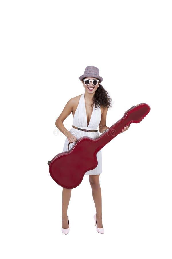 Szczęśliwa młoda kobieta jest ubranym okulary przeciwsłonecznych pozuje z gitarą fotografia royalty free