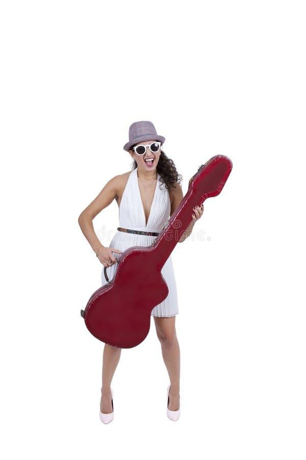 Szczęśliwa młoda kobieta jest ubranym okulary przeciwsłonecznych pozuje z gitarą fotografia stock