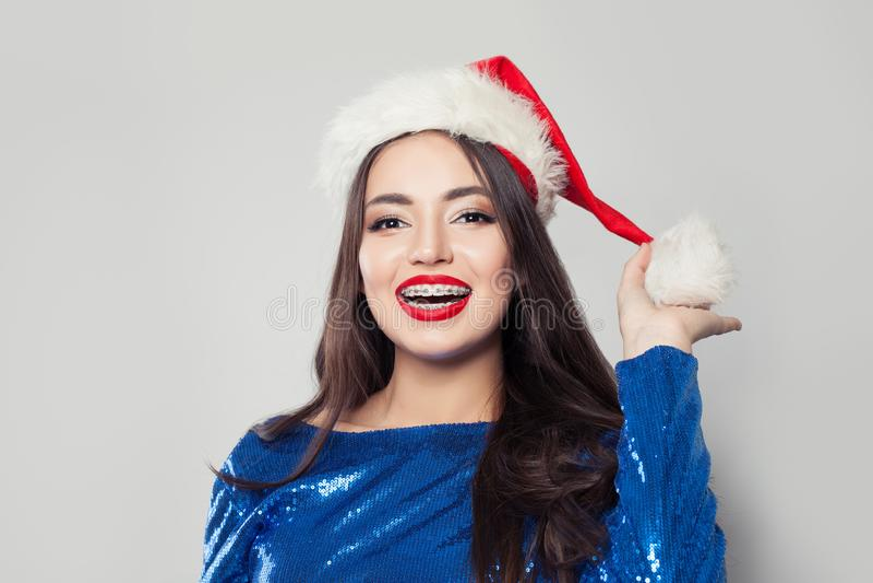 Szczęśliwa młoda kobieta jest ubranym Santa ono uśmiecha się i kapelusz w brasach zdjęcie stock