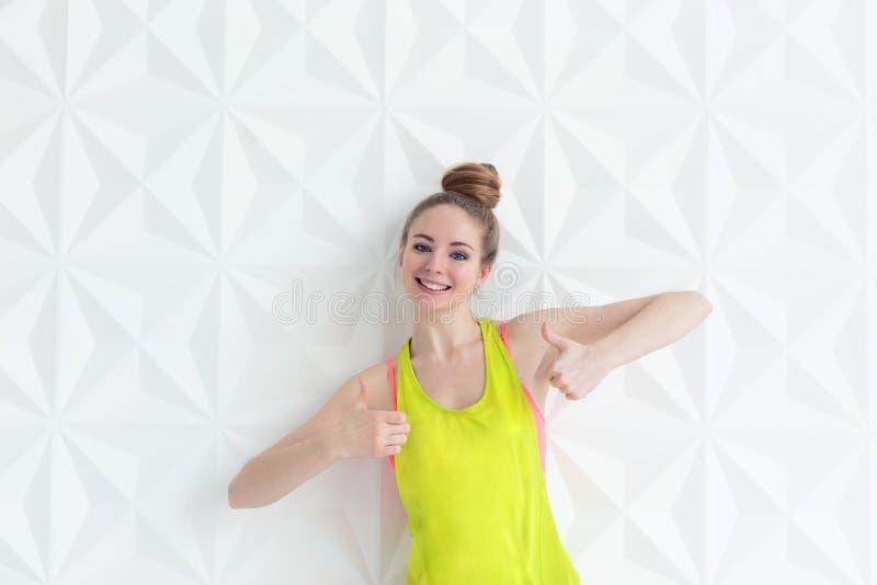 Szczęśliwa młoda kobieta jest ubranym sportswear seans wręcza kciuk up podpisuje fotografia royalty free
