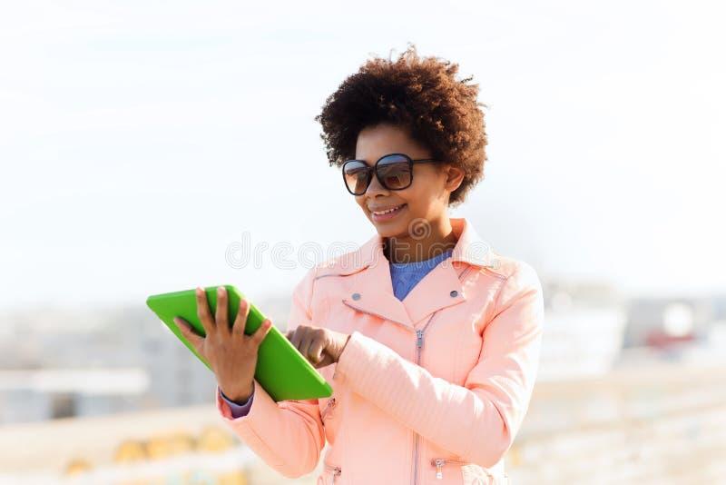 Szczęśliwa młoda kobieta lub nastoletnia dziewczyna z pastylka komputerem osobistym zdjęcia stock