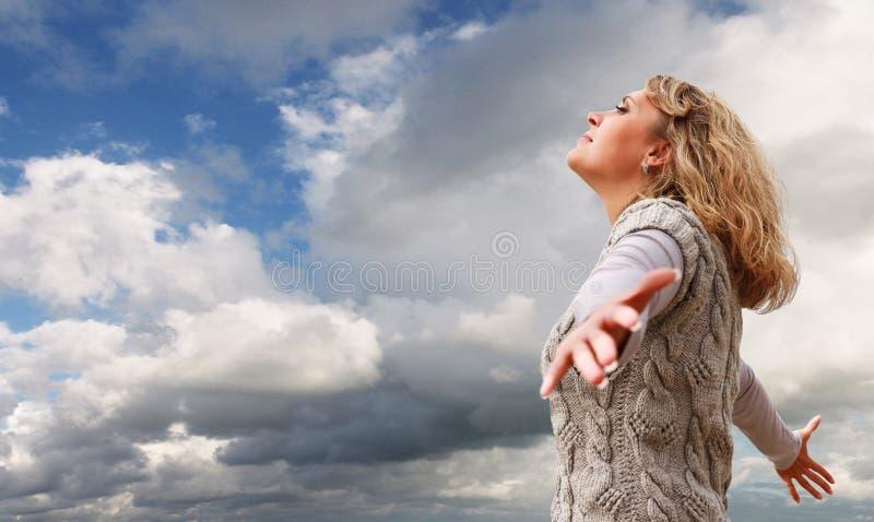 Szczęśliwa młoda kobieta na błękitny chmurnego nieba widok zdjęcie stock