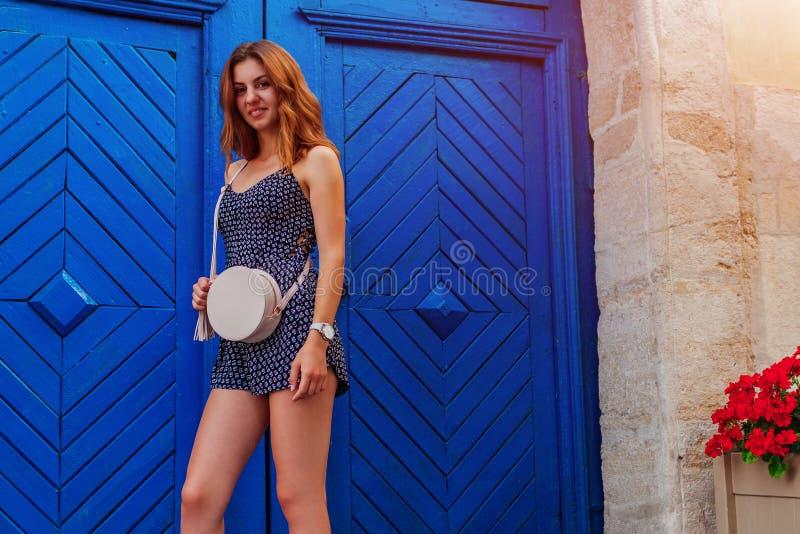 Szczęśliwa młoda kobieta ono uśmiecha się przeciw błękitnemu drewnianemu drzwi Plenerowy portret piękna szkoły wyższa dziewczyna  fotografia stock