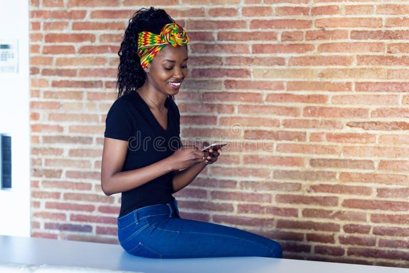 Szczęśliwa młoda kobieta opowiada na telefonie komórkowym podczas gdy siedzący na stole przed ścianą obraz royalty free