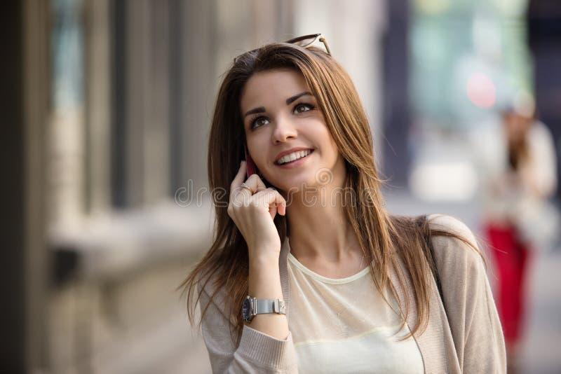 Szczęśliwa młoda kobieta opowiada na telefonie komórkowym przy miasto stylu życia ulicznym portretem obrazy stock