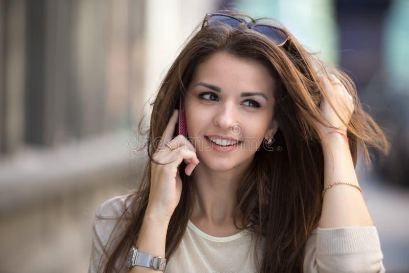 Szczęśliwa młoda kobieta opowiada na telefonie komórkowym przy miasto stylu życia ulicznym portretem zdjęcie stock