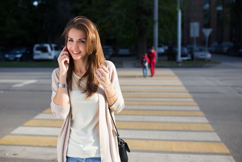 Szczęśliwa młoda kobieta opowiada na telefonie komórkowym przy miasto stylu życia ulicznym portretem zdjęcia stock
