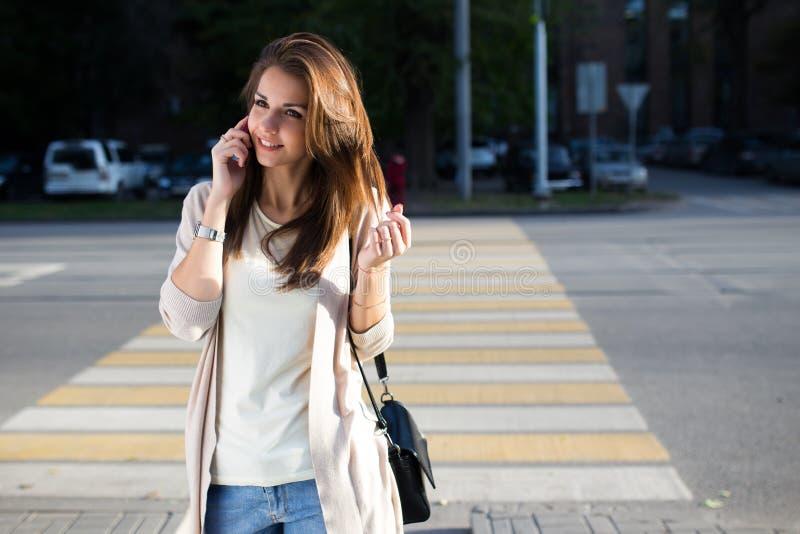 Szczęśliwa młoda kobieta opowiada na telefonie komórkowym przy miasto stylu życia ulicznym portretem zdjęcie royalty free