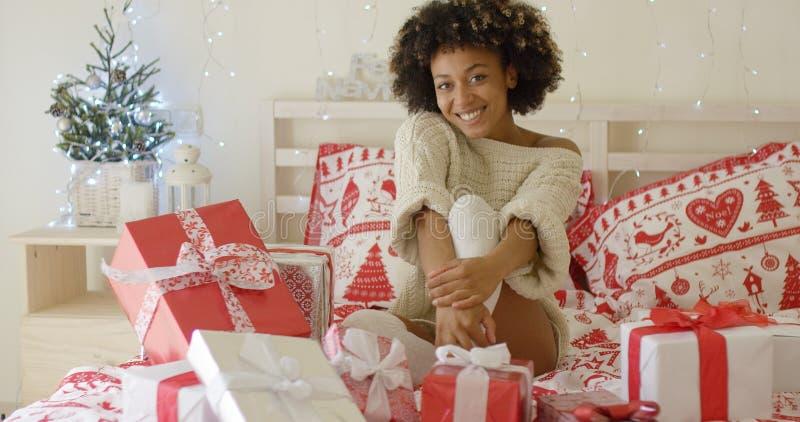 Szczęśliwa młoda kobieta otaczająca Bożenarodzeniowymi prezentami obraz royalty free