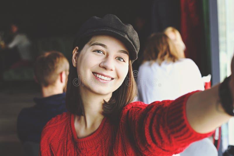 Szczęśliwa młoda kobieta pije cappuccino, używa pastylka komputer i opowiada na telefonie w, latte, macchiato, herbata, sklep z k obrazy royalty free