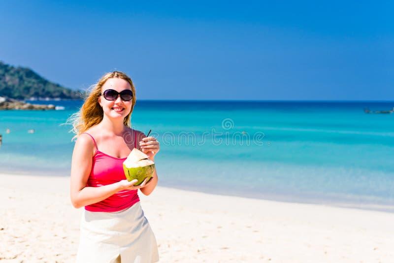Szczęśliwa młoda kobieta pije kokosowego mleko obrazy stock