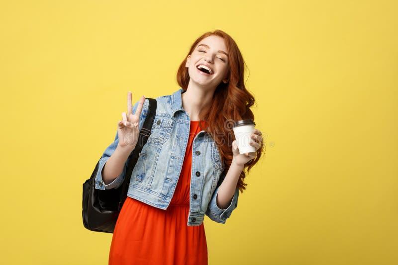 Szczęśliwa młoda kobieta pokazuje dwa palca z rozporządzalną filiżanką nad odosobnionym jaskrawym żółtym tłem zdjęcie royalty free