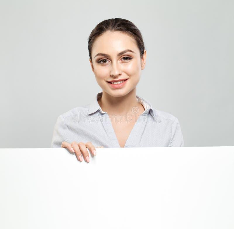 Szczęśliwa młoda kobieta pokazuje signboard z pustym copyspace terenem dla advertisiment lub wiadomości tekstowej Edukacja i bizn fotografia royalty free