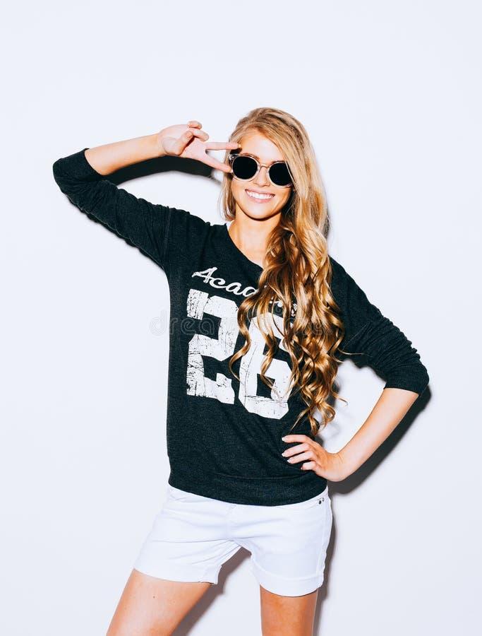 Szczęśliwa młoda kobieta Pokazuje zwycięstwo Podpisuje wewnątrz okulary przeciwsłonecznych Na Białym tle salowy kolor ciepła obraz stock