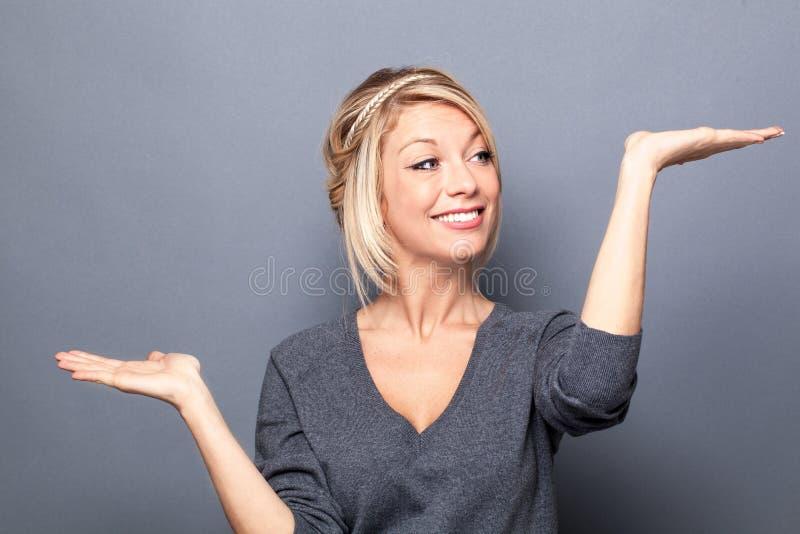Szczęśliwa młoda kobieta porównuje nierównomiernego wybór produkt fotografia royalty free