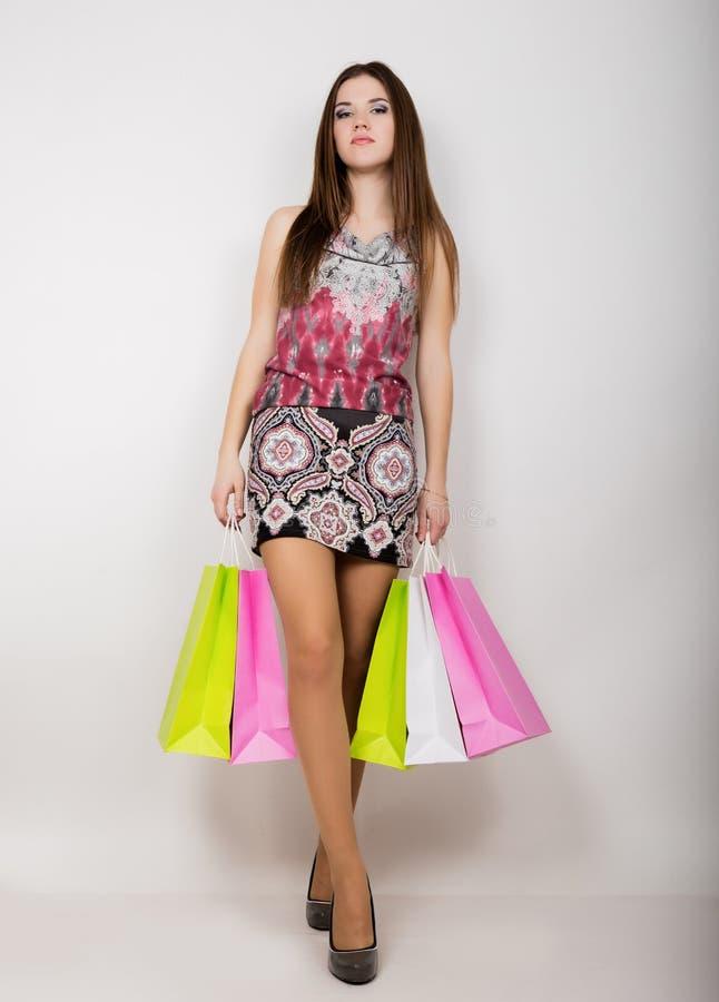 Szczęśliwa młoda kobieta pozuje z torba na zakupy fotografia royalty free