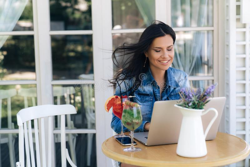 Szczęśliwa młoda kobieta pracuje na internecie, siedzi przy stołem w kawiarni i robi zakupom online, właśnie płacił bankiem fotografia stock