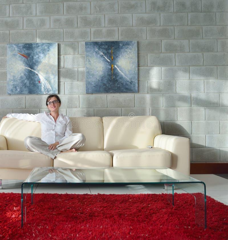 Szczęśliwa młoda kobieta relaksuje w domu na kanapie zdjęcia stock