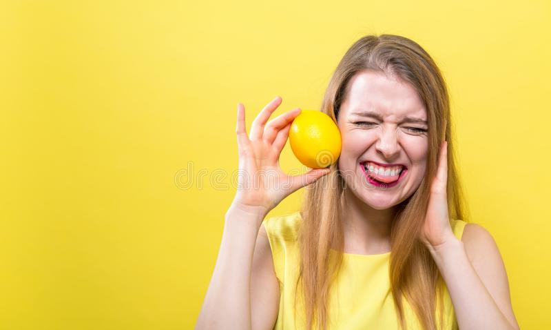 Szczęśliwa młoda kobieta trzyma cytrynę obrazy stock