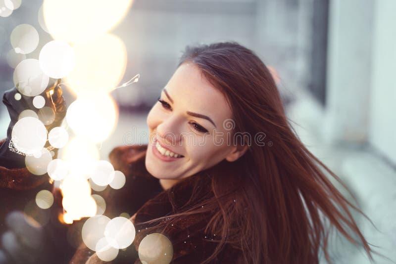 Szczęśliwa młoda kobieta trzyma czarodziejskich światła w zimnej zimy plenerowej pogodzie obrazy royalty free