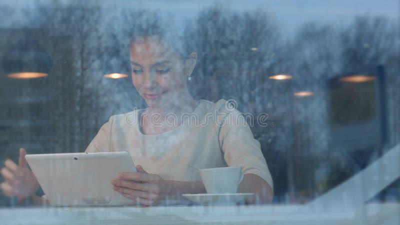 Szczęśliwa młoda kobieta używa cyfrową pastylkę w sklep z kawą zdjęcia royalty free