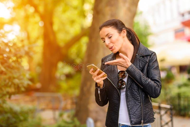 Szczęśliwa młoda kobieta używa jej telefon w miastowym środowisku zdjęcie stock