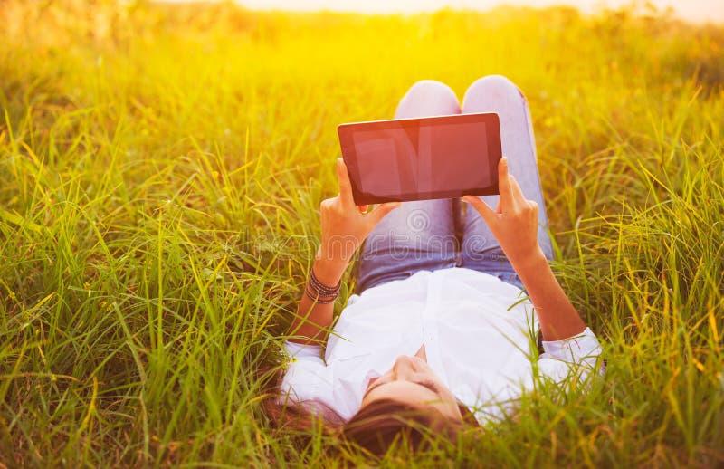 Szczęśliwa młoda kobieta Używa pastylkę fotografia stock