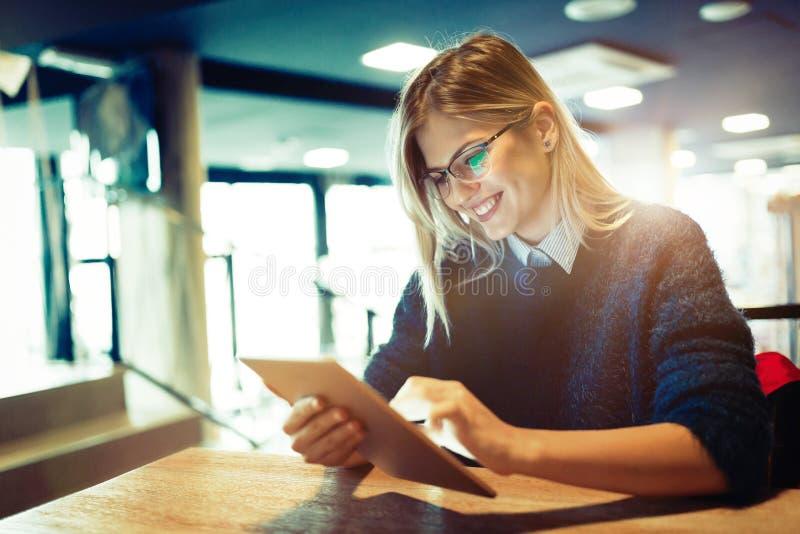 Szczęśliwa młoda kobieta używa pastylkę przy sklep z kawą obraz royalty free