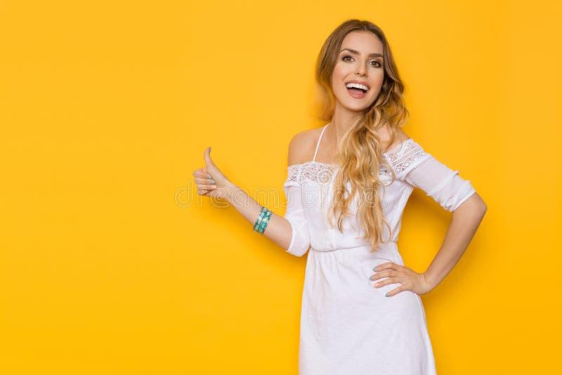 Szczęśliwa młoda kobieta W biel sukni Pokazuje kciuk Up fotografia stock