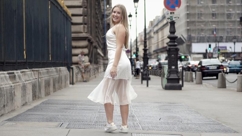 Szczęśliwa młoda kobieta w bielu smokingowy pozować na tła miasta ulicach akcja Atrakcyjna blondynka ono uśmiecha się wewnątrz i  zdjęcia stock