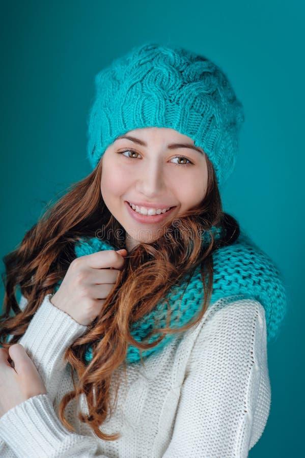 Szczęśliwa młoda kobieta w dzianina szaliku i kapeluszowym błękicie fotografia royalty free