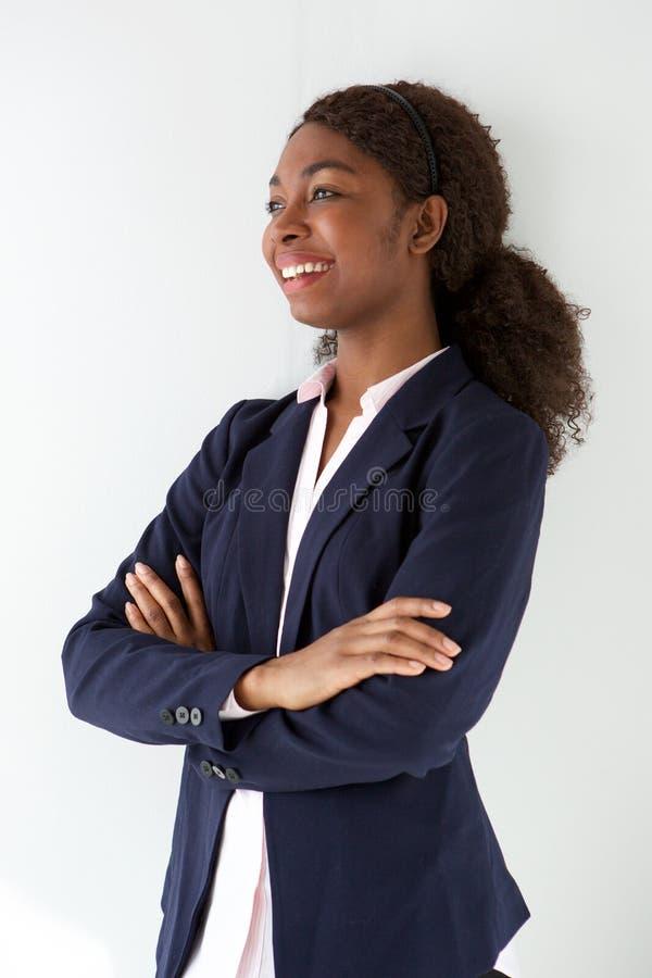 Szczęśliwa młoda kobieta w garnitur pozyci z jej rękami krzyżować i patrzeją daleko od zdjęcia stock