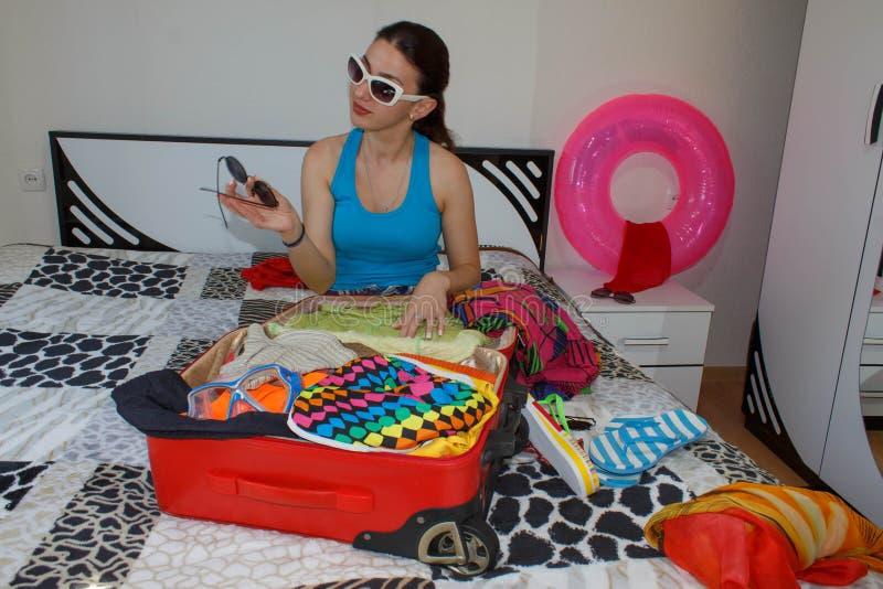 Szczęśliwa młoda kobieta w kolorowym lato stroju blisko czerwonej napchanej walizki zdjęcia stock