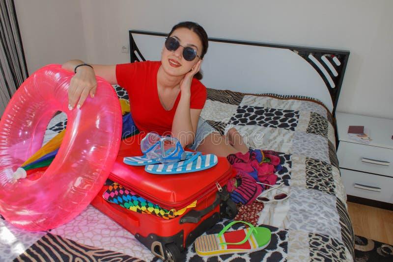 Szczęśliwa młoda kobieta w kolorowym lato stroju obsiadaniu blisko czerwieni obraz stock