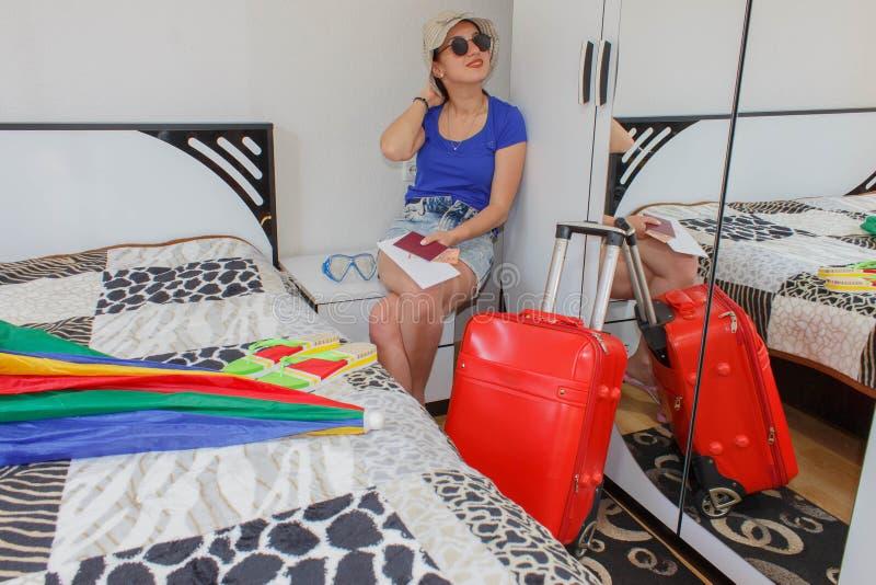 Szczęśliwa młoda kobieta w kolorowym lato stroju obsiadaniu blisko czerwonej napchanej walizki fotografia royalty free