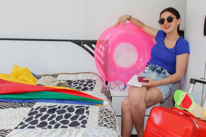 Szczęśliwa młoda kobieta w kolorowym lato stroju obsiadaniu blisko czerwonej napchanej walizki, ono uśmiecha się fotografia stock