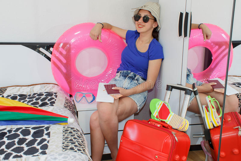 Szczęśliwa młoda kobieta w kolorowym lato stroju obsiadaniu blisko czerwonej napchanej walizki, ono uśmiecha się obrazy stock