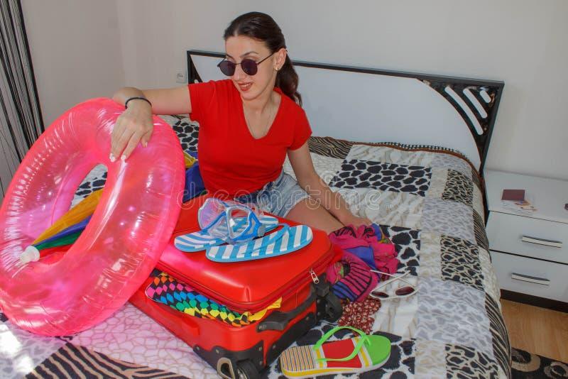 Szczęśliwa młoda kobieta w kolorowym lato stroju obsiadaniu blisko czerwonej napchanej walizki, ono uśmiecha się obrazy royalty free