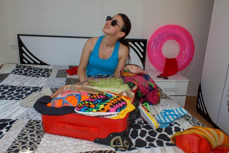 Szczęśliwa młoda kobieta w kolorowym lato stroju obsiadaniu blisko czerwonej napchanej walizki, ono uśmiecha się obraz stock