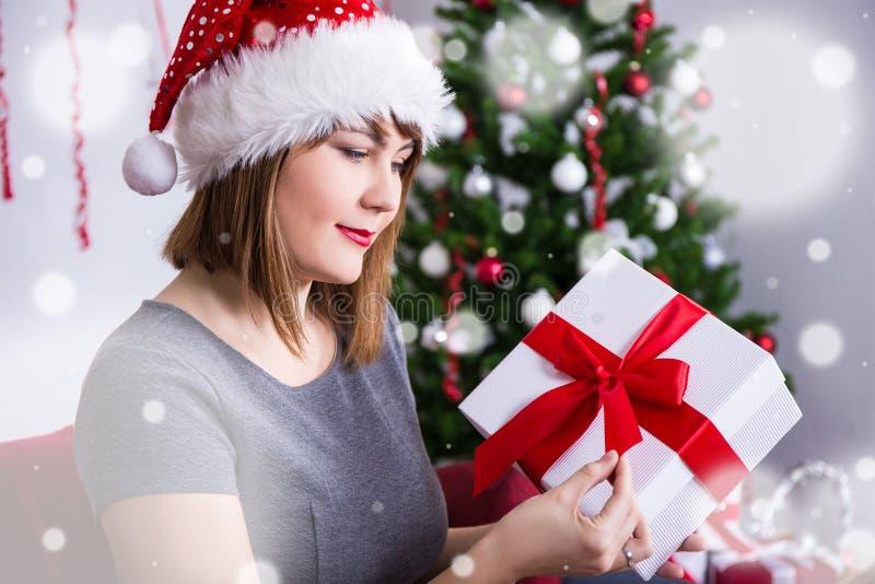 Szczęśliwa młoda kobieta w Santa otwarcia prezenta kapeluszowym pudełku blisko bożych narodzeń t fotografia stock