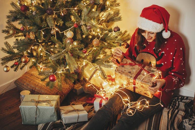 Szczęśliwa młoda kobieta w Santa otwarcia prezenta kapeluszowym pudełku przy złotym beauti zdjęcia stock